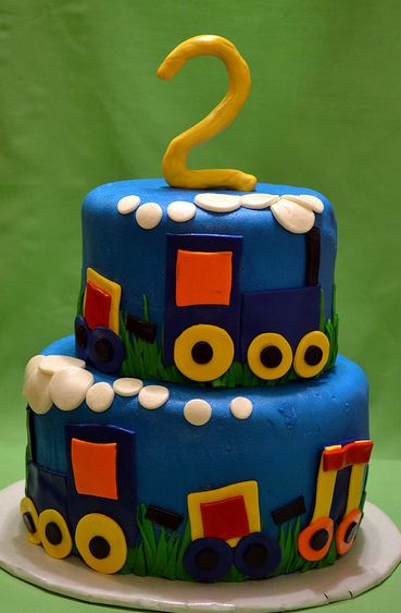 Two tier round blue second birthday cake with trains and the number 2 on top