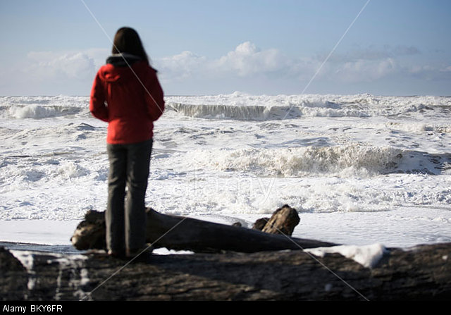 BKY6FR A woman watching ocean waves in a turbulent sea.